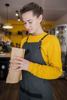 Vista laterale del barista tenendo il pacchetto di caffè