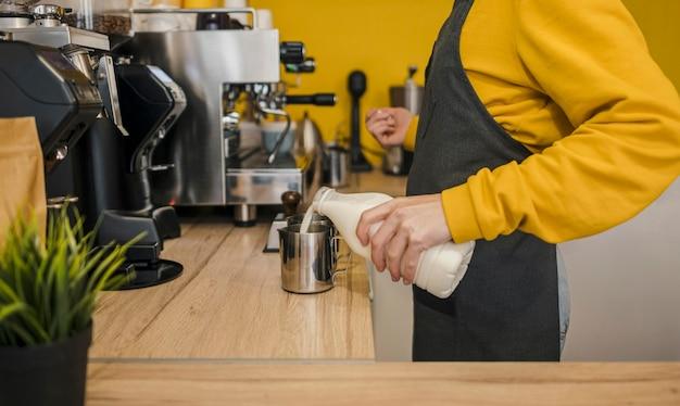 Vista laterale del barista versando il latte