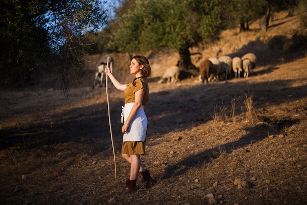 Vista laterale del bastone femminile della tenuta del coltivatore nel campo