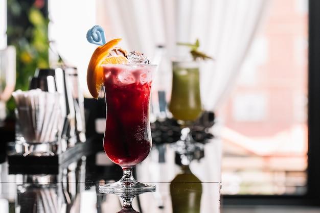 Vista laterale del bicchiere di cocktail con rum sciroppo di fragole e limone decorato con fetta d'arancia a sfondo barra