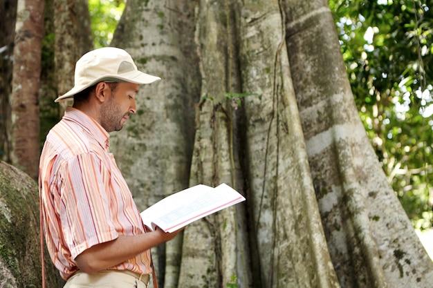 Vista laterale del botanico maschio caucasico in cappello panama e camicia a righe che esplora le specie al lavoro sul campo nella foresta tropicale, in piedi di fronte a una grande pianta, leggendo le informazioni dell'albero emergente nel manuale