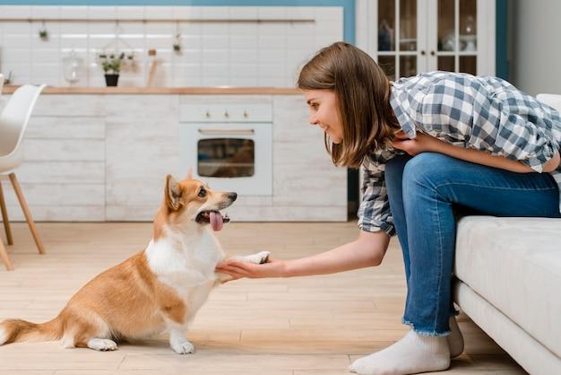 Vista laterale del cane che dà zampa al proprietario