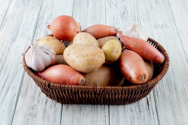 Vista laterale del canestro in pieno delle verdure come cipolla della patata dell'aglio su fondo di legno