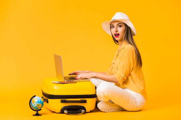 Vista laterale del cappello da portare della donna mentre lavorando al computer portatile in cima ai bagagli