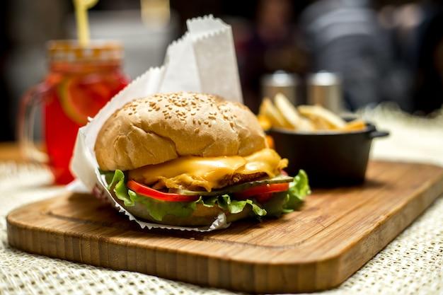 Vista laterale del cetriolo del pomodoro del formaggio della lattuga del bordo di legno dell'ob dell'hamburger del pollo