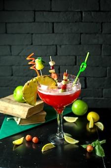 Vista laterale del cocktail della margarita della calce della fragola con un pezzo di ananas in vetro su oscurità