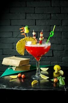 Vista laterale del cocktail di alcool esotico rosso con un pezzo di ananas in vetro sul tavolo