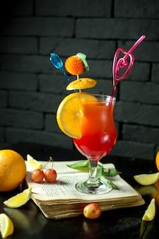 Vista laterale del cocktail esotico con fetta di limone e paglia in un bicchiere su oscurità