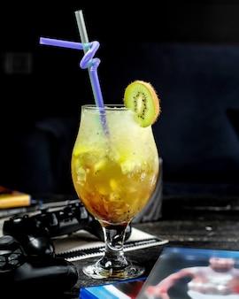 Vista laterale del cocktail ghiacciato del kiwi in vetro su oscurità