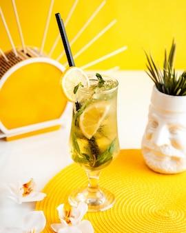 Vista laterale del cocktail mojito con ghiaccio e limone in un bicchiere su giallo