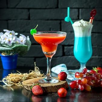 Vista laterale del cocktail rosso in vetro con la frutta fresca sulla tavola di legno