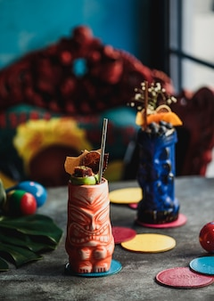 Vista laterale del cocktail tiki con frutto della passione su un tavolo