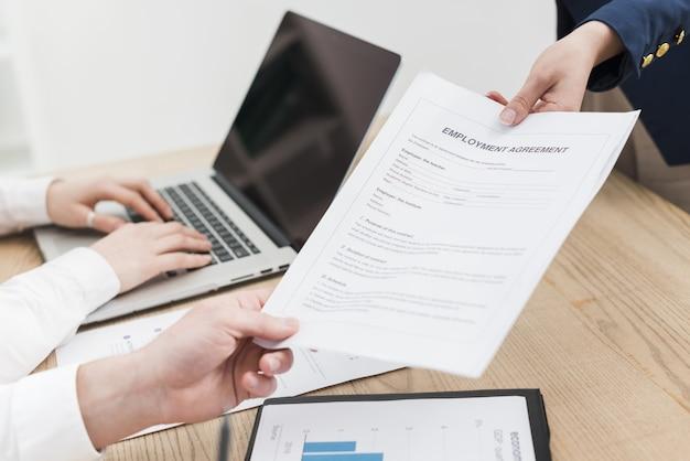Vista laterale del contratto d'offerta della donna durante il colloquio di lavoro
