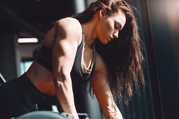 Vista laterale del culturista femminile caucasico muscolare che risolve in palestra. diventa leggendario.