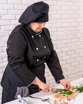 Vista laterale del cuoco unico femminile che taglia erba cipollina a pezzi