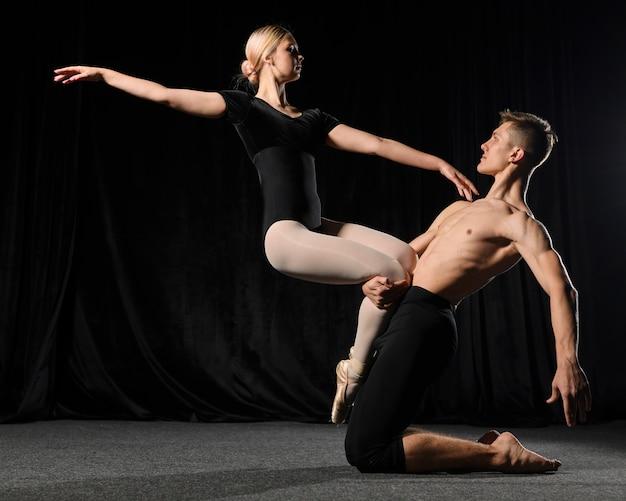 Vista laterale del dancing delle coppie di balletto nel body con lo spazio della copia