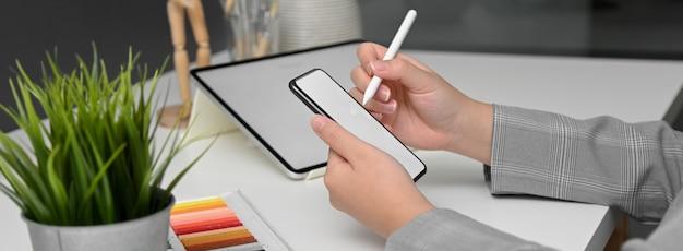 Vista laterale del designer femminile che lavora con tablet mock-up mentre cerca informazioni sullo smartphone
