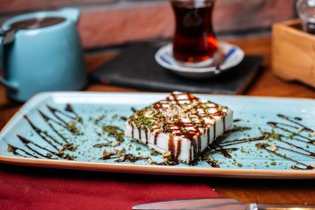 Vista laterale del dessert di delizia turca con noci e polvere di pistacchio sul tavolo
