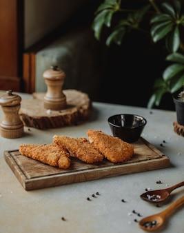 Vista laterale del filetto di pollo fritto nella briciola di pane con salsa su un bordo di legno