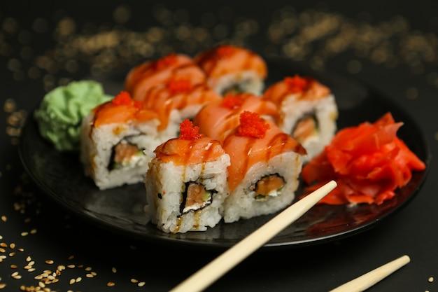 Vista laterale del formaggio cremoso del wasabi dello zenzero del riso di maki di color salmone