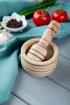 Vista laterale del frantoio dell'aglio con le verdure e pepe nero sulla superficie blu del panno e sul fondo di legno