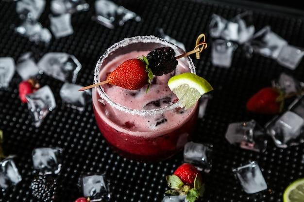 Vista laterale del ghiaccio della calce del lampone della mora dell'alcool del cocktail della bacca