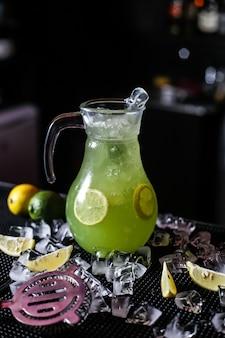 Vista laterale del ghiaccio della calce dell'acqua frizzante del limone della brocca della limonata dell'agrume