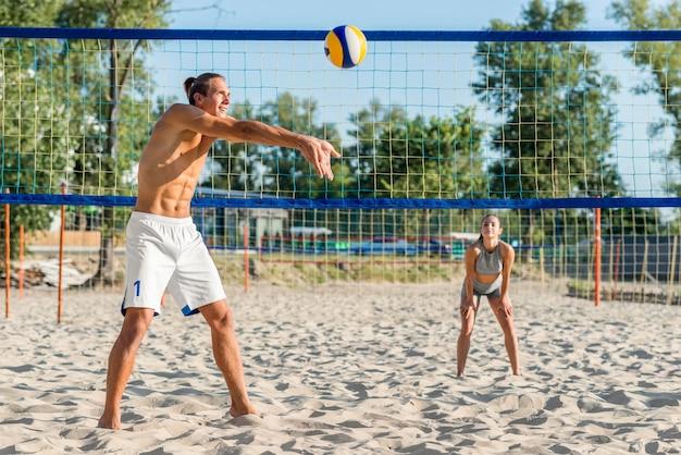 Vista laterale del giocatore di pallavolo maschile sulla spiaggia con la donna che gioca