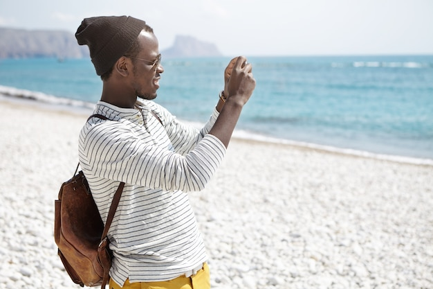 Vista laterale del giovane afroamericano con lo zaino, in cappello e camicia a strisce che prendono le foto della spiaggia che sta sulla spiaggia da solo