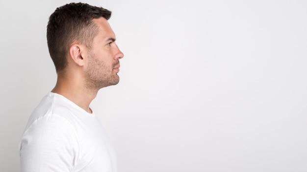 Vista laterale del giovane che sta contro il fondo bianco