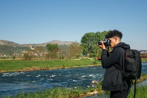 Vista laterale del giovane che usando la macchina fotografica di dslr che cattura maschera