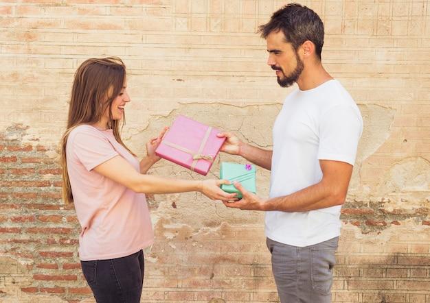 Vista laterale del giovane e della donna che dà il regalo di san valentino a vicenda