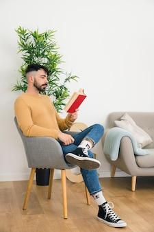 Vista laterale del giovane serio bello che si siede sulla sedia che legge il libro