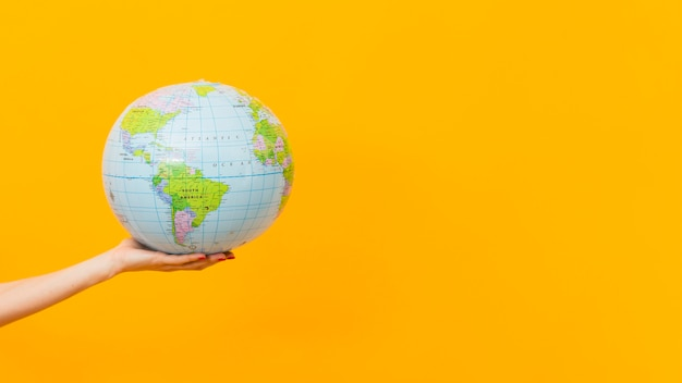 Vista laterale del globo della terra della tenuta della mano con lo spazio della copia