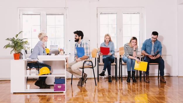 Vista laterale del gruppo di giovani seduti e in attesa annoiati in fila con una cartella per un colloquio di lavoro mentre uno di loro ha una conversazione con l'imprenditore.