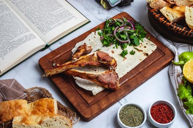 Vista laterale del kebab della costola dell'agnello con le erbe e la cipolla su un bordo di legno