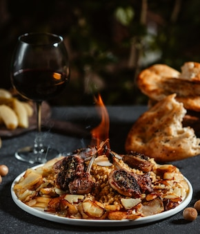 Vista laterale del kebab delle costole dell'agnello con le patate fritte su una tavola nera