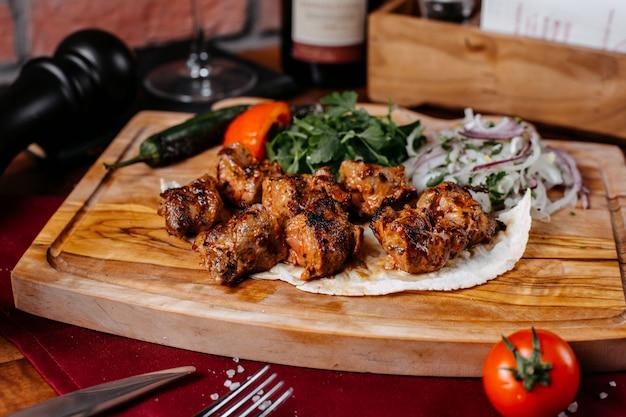 Vista laterale del kebab di pollo con cipolle ed erbe su una tavola di legno