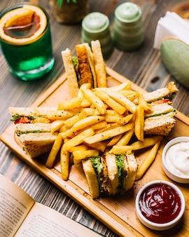 Vista laterale del ketchup della maionese delle patate fritte del cetriolo del pomodoro del pollo del pane tostato del panino di club