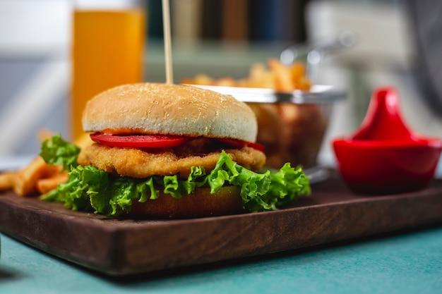 Vista laterale del ketchup delle patate fritte del formaggio del pomodoro della lattuga dell'hamburger del pollo
