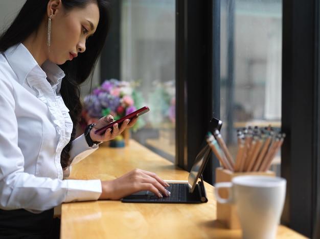Vista laterale del libero professionista femmina utilizza lo smartphone mentre si lavora con la tavoletta digitale sulla barra nella caffetteria