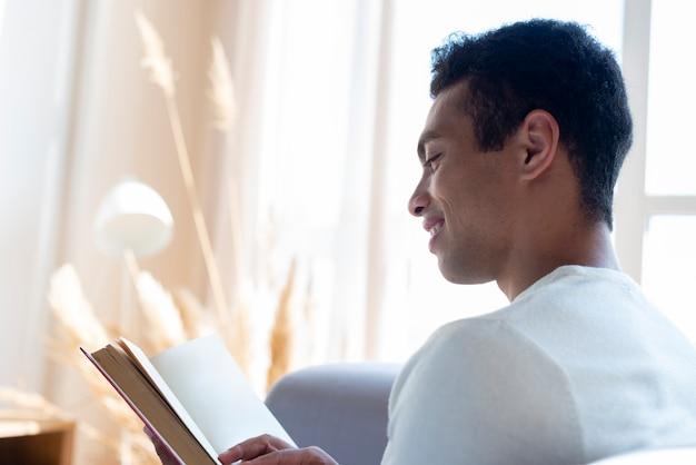 Vista laterale del libro di lettura dell'uomo