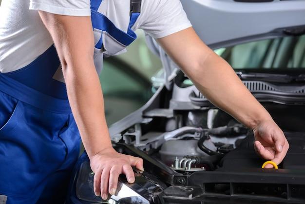 Vista laterale del meccanico che controlla l'olio per motori in un'automobile.