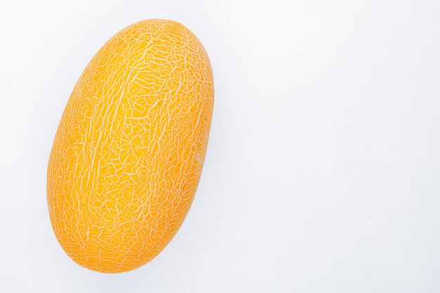 Vista laterale del melone su fondo bianco con lo spazio della copia