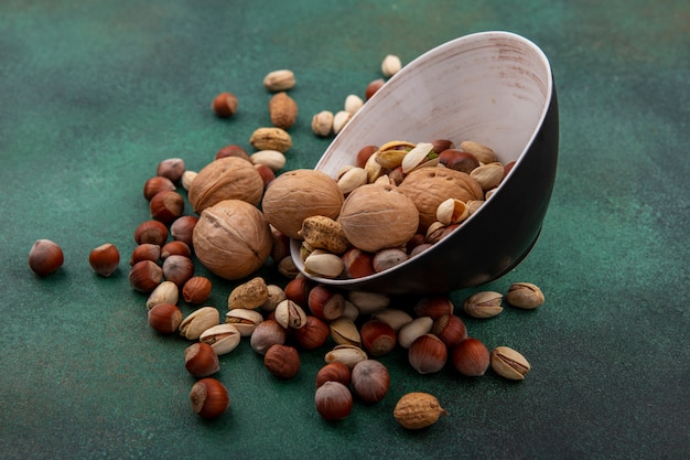 Vista laterale del mix di noci noci pistacchi nocciole e arachidi in una ciotola su una superficie verde
