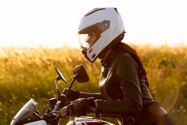 Vista laterale del motociclista femminile con il casco