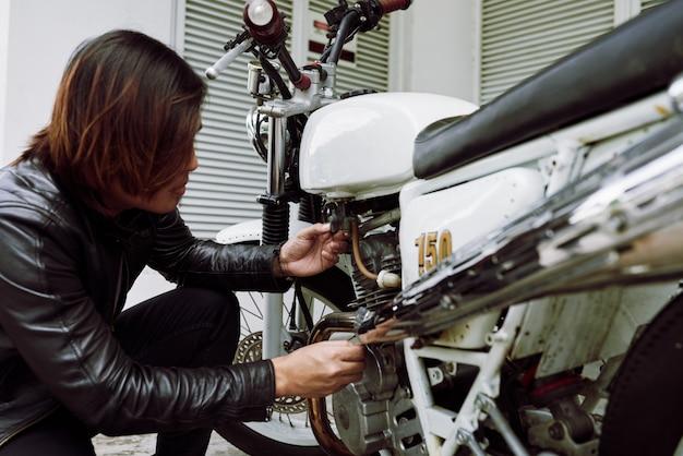 Vista laterale del motociclista ispezionando la sua bici prima di un giro