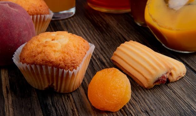 Vista laterale del muffin con albicocche secche e biscotti su legno rustico