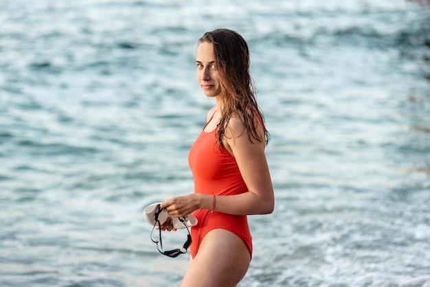 Vista laterale del nuotatore femminile che tiene gli occhialini da nuoto