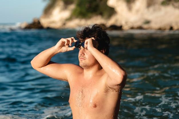 Vista laterale del nuotatore maschio che indossa gli occhiali da nuoto